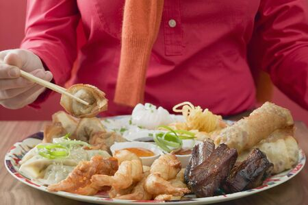 waist deep: Woman eating Asian appetisers LANG_EVOIMAGES