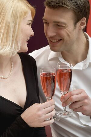 25 to 30 year olds: Couple clinking glasses of sparkling wine