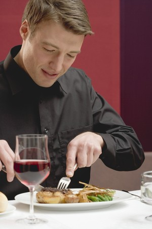 30 to 35 year olds: Man eating steak in restaurant