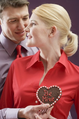 25 to 30 year olds: Man giving woman chocolate heart with the words Be Mine