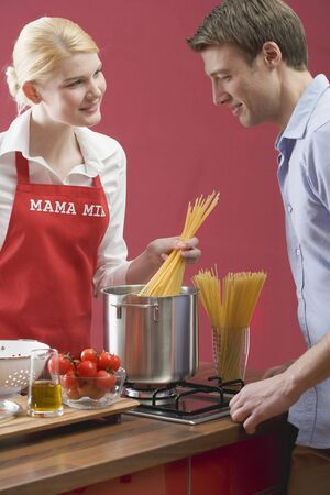 old gas stove: Couple cooking spaghetti with tomatoes LANG_EVOIMAGES
