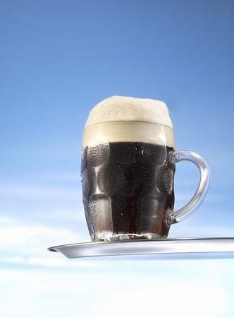 schwarzbier: Dunkles Bier im Glaskrug auf Tablett