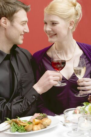 connoisseurs: Elegant couple raising glasses of wine