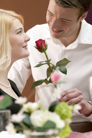 25 to 30 year olds: Man giving woman a red rose LANG_EVOIMAGES