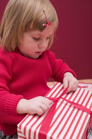 undoing: Small girl undoing ribbon on Christmas parcel
