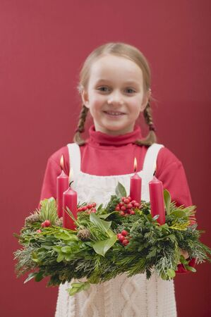 ignited: Small girl holding Advent wreath with burning candles