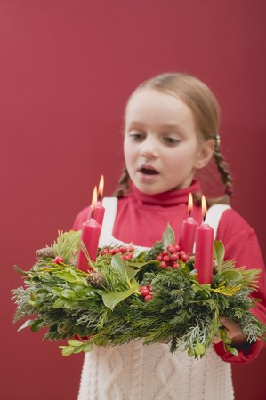 blowing out: Small girl blowing out candles on Advent wreath