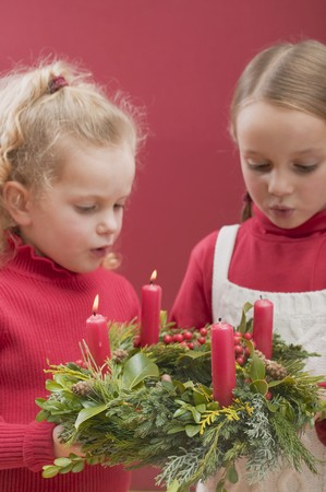 blowing out: Two small girls blowing out candles on Advent wreath