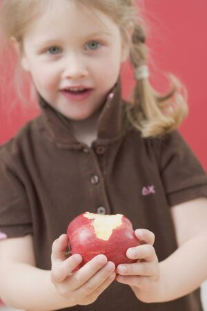 partly: Little girl holding a partly eaten apple LANG_EVOIMAGES