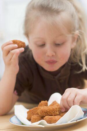 nuggets de poulet: Petite fille mangeant des nuggets de poulet