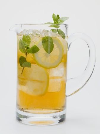 lemon slices: T� freddo con fette di limone e menta fresca in brocca di vetro