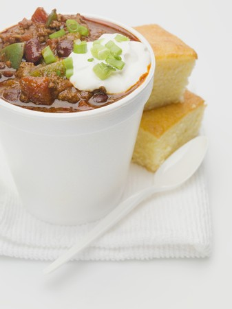 cornbread: Chili con carne with sour cream in polystyrene cup, cornbread LANG_EVOIMAGES