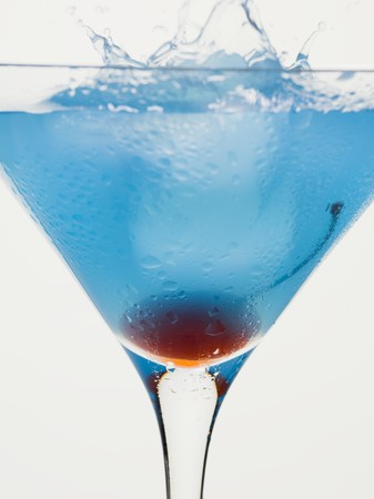 squirted: Blue Cura�ao cocktail with cocktail cherry and ice cube