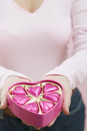 hold ups: Woman holding box of heart-shaped chocolates LANG_EVOIMAGES