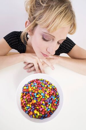 25 to 30 year olds: Woman looking pensively at coloured chocolate beans LANG_EVOIMAGES
