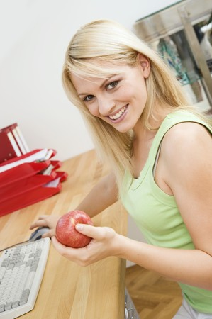 25 to 30 year olds: Woman with an apple at her desk