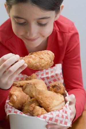 5 10 year old girl: Little girl eating deep-fried chicken drumsticks