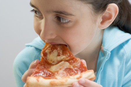 5 10 year old girl: Little girl eating slice of pizza LANG_EVOIMAGES