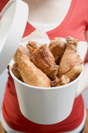 waist deep: Woman holding bucket of deep-fried chicken drumsticks LANG_EVOIMAGES