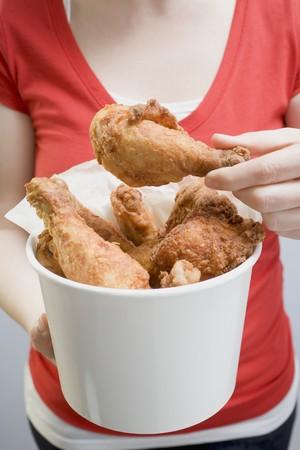 waist deep: Woman holding deep-fried chicken drumsticks