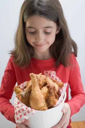 5 10 year old girl: Little girl holding deep-fried chicken drumsticks