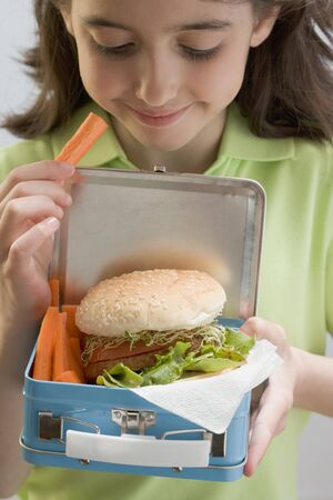 casual clothing 12 year old: Girl holding lunch box containing burger & carrots