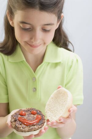 5 10 year old girl: Little girl holding opened burger with ketchup face