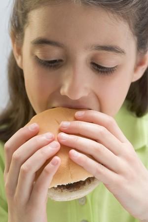 5 10 year old girl: Little girl eating hamburger