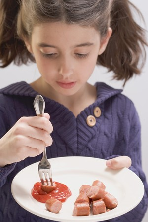 scalded sausage: Little girl eating frankfurters with ketchup