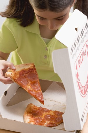 5 10 year old girl: Little girl taking slice of pizza out of pizza box