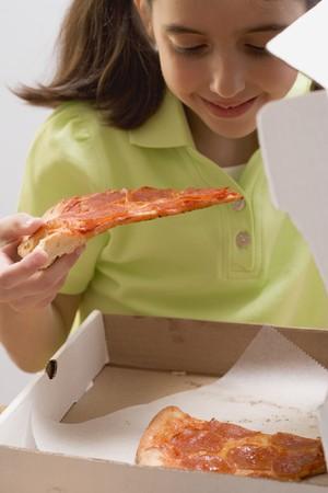 pizza box: Ni�a que sostiene la porci�n de pizza sobre la caja de pizza