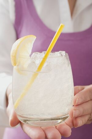 hold ups: Woman holding glass of lemonade with straw