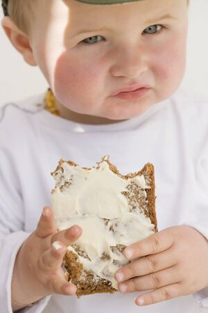 eat smeared: Baby holding a partly-eaten slice of bread and butter