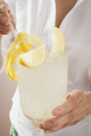 Woman holding a glass of lemonade LANG_EVOIMAGES