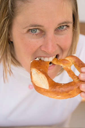 30 to 35 year olds: Woman biting into a pretzel