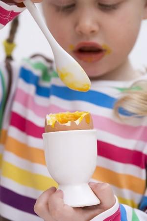 Little girl eating soft-boiled egg