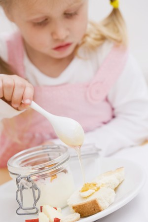trickling: Little girl trickling honey onto bread and butter