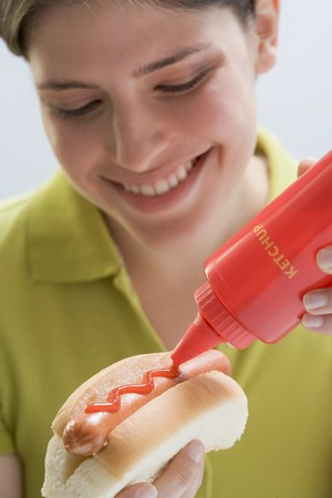 squirting ketchup: Young woman putting ketchup on hot dog LANG_EVOIMAGES