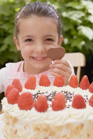 gateau: Little girl with chocolate heart behind large strawberry gateau