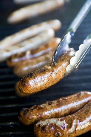 grill tongs sausage: Sausages on a barbecue (close-up)