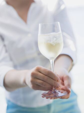 blouses: Woman holding glass of white wine with ice cubes out of doors