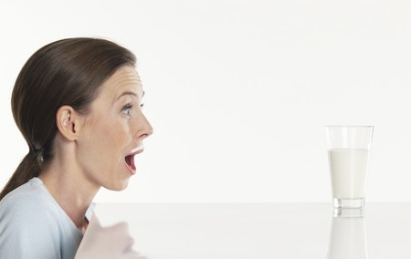 25 to 30 year olds: Young woman looking at glass of milk, gasping LANG_EVOIMAGES