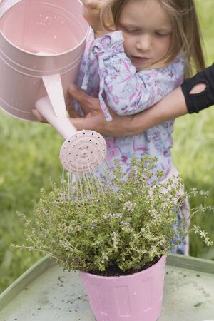 water thyme: Mother helping daughter to water thyme