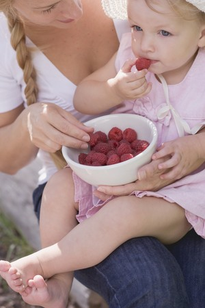 eating area: Mother and young daughter eating raspberries