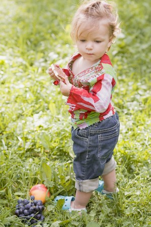 baby rice: Little girl holding rice cake in grass LANG_EVOIMAGES