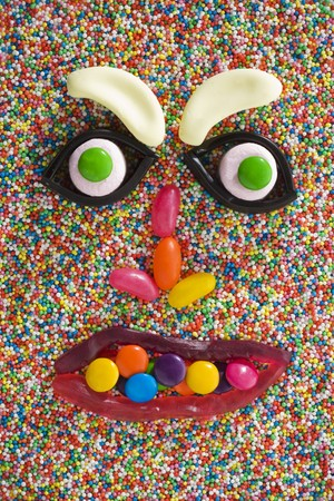 hundreds and thousands: A face made from sweets on hundreds and thousands LANG_EVOIMAGES