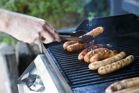 grill tongs sausage: Sausages on a barbecue