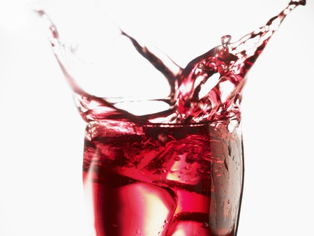 squirted: Cranberry juice splashing out of a glass