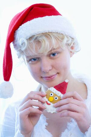 16 to 17 year olds: Girl in Father Christmas hat holding Father Christmas biscuit