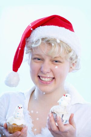 16 to 17 year olds: Girl holding muffins with marzipan snowmen LANG_EVOIMAGES
